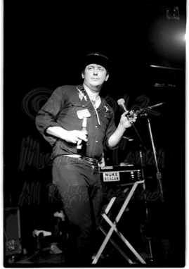"""Mr. Langford about to inform the audience of some matter or another, between songs. Note the """"Nuke Reagan"""" sticker! This will date the picture somewhat, but how much has really changed in the meantime? From the I-Beam, SF on May 4, 1987"""