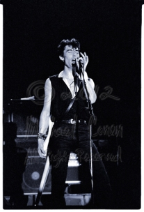 """Pete Farndon adding the backing vocal lines, and in the spotlight, with his """"gunslinger"""" pose"""