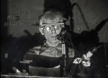 Don Joyce recites from behind the glass of the DJ booth at the I-Beam